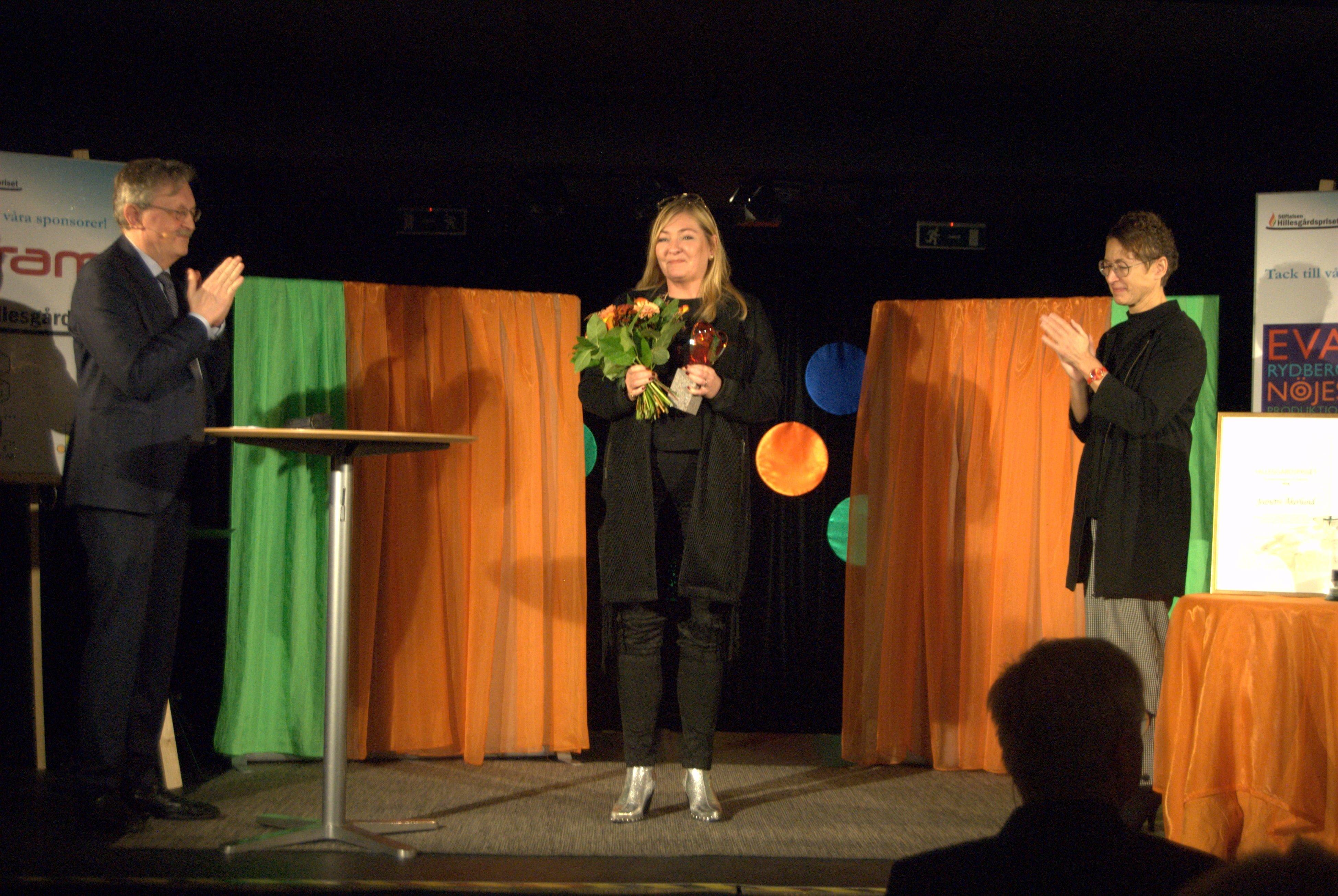Jeanette Åkerlund tar emot Hillesgårdspriset för medmänsklighet och förlåtelse av Kerstin Persson, kommunstyrelsens ordförande i Klippan. under överinseende av juryns ordförande Karl-Erik Edris.