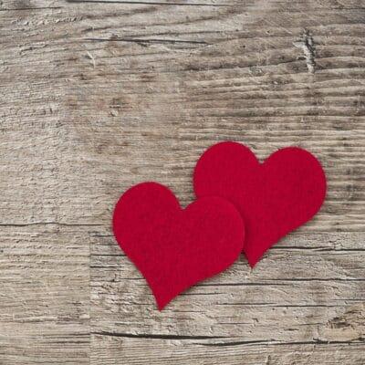 Två röda hjärtan på en trävägg.